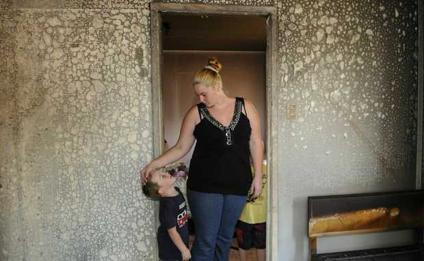 Danni Barron and her son Lochlyen survey fire damage to their Oakey home.