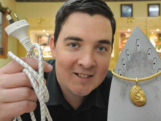 Gemmologist Matthew Gray from Haigh's Jewellers with a 9ct yellow gold diamond set shell worth $2700 on a 9ct yellow gold mesh link chain worth $2100 and the practical iron.