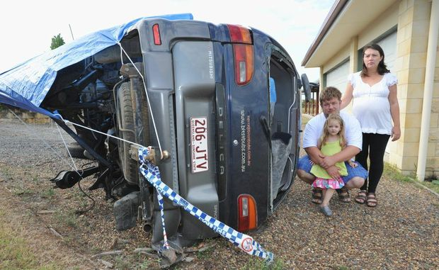 Kerry and Shane Mandrek and daughter Jessica (3) with their wrecked family vehicle.