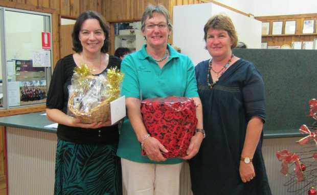 Puddy Chandler (centre) gets her gift for 10 years service as president with Maranoa Council CEO Julie Reitano and Vikki Hartley (inaugural secretary) at recent AGM of Injune District Tourism Assoc. Photo Contributed