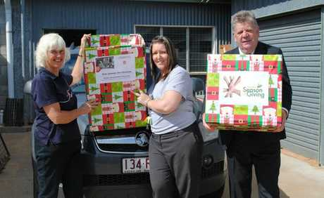 IN THE SPIRIT: Salvation Army volunteers Kathy Rosenberger and Michelle Jones are helped packing food hampers by mayor Wayne Kratzmann.