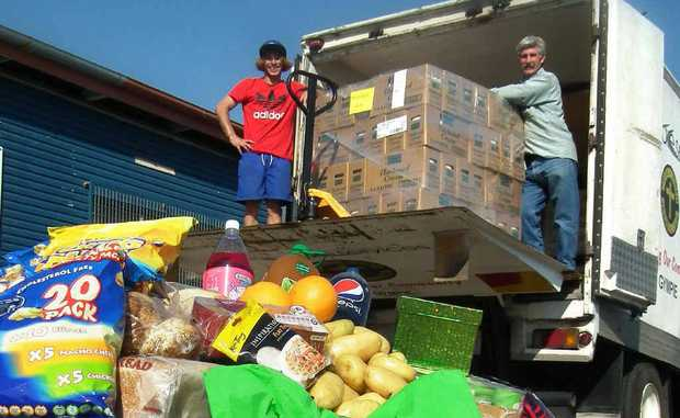 Matthew Davis and Col Williams start unloading the crates of food in preparation for the free food giveaway tomorrow.