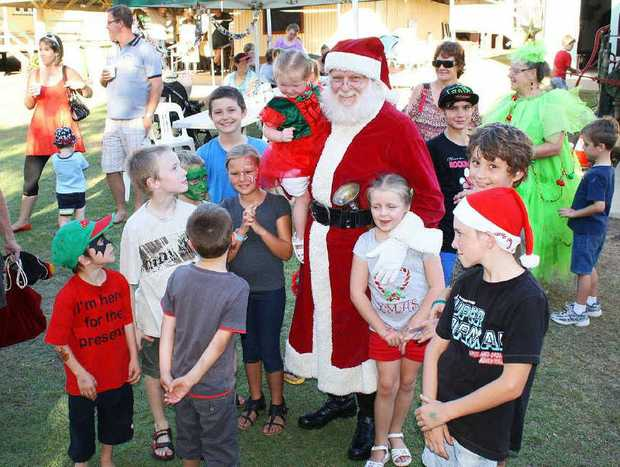 CENTRE OF ATTENTION: Santa Claus arrives all smiles at Laidley's Pioneer Village and is an instant hit.
