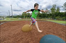 Liam Smith leaps around one of the new play grounds at Colleges Crossing. The recreation park has reopened.