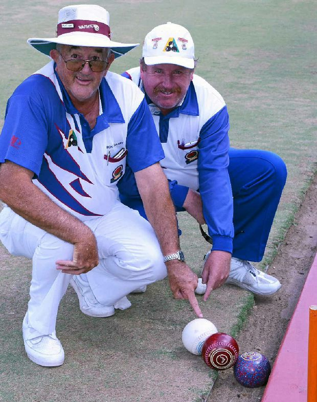 CLOSE: Mick O'Leary and Tony Heffernan place three bowls near the ditch to reproduce an amazing coincidence at Warwick Bowls Club.
