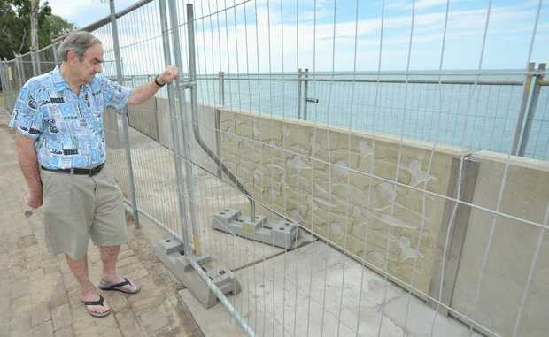 Urangan resident Bevan Hancock takes a close look at the first panels in the replacement seawall.