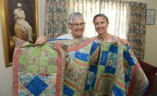 Hospice admininstration co-ordinator Karen Lavin (right) with Eileen Vass and her quilt that was raffled and money donated to Hospice Ipswich.