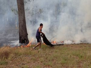 A local resident helps to fight the fire with a damp hession sack.