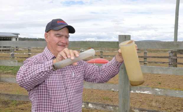 Wellcamp farmer Ken Baldwin empties his rain gauge yesterday