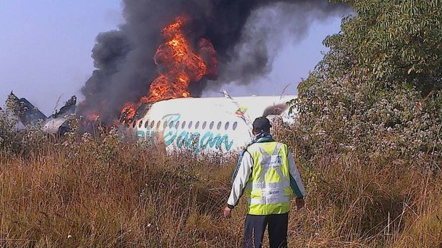 This photo taken on December 25, 2012 shows a man walking the fuselage of an Air Bagan passenger plane burn after it crashed near Heho airport in Myanmar's eastern Shan state. The Myanmar ageing Fokker-100 plane carrying 65 passengers including foreign tourists crash-landed in eastern Shan state, leaving two people dead and 11 others injured, the airline and officials said.   AFP PHOTO