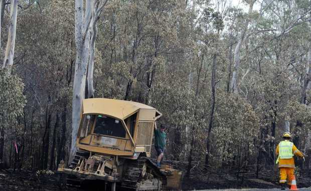 Bulldozer driver Ken Stanton takes a break while pushing over burnt out trees that could potentially have fallen across the Maryborough-Hervey Bay Rd.