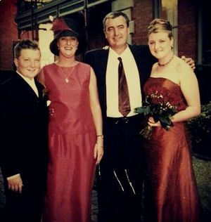 Rocking the burnt orange bridesmaid's dress, Carlie Walker (right) in a family photo with her brother Matt, mum Julie and dad David.