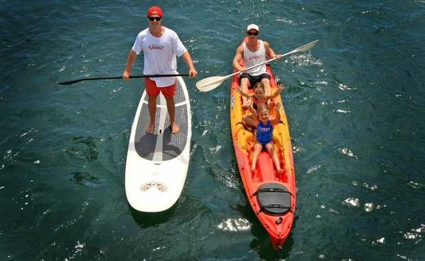 Mick Munday takes Kaitlin 7 and Zoe 4 McMahon for a kyak while Paddleboard expert Dean Kenny tags along. Photo: Blainey Woodham / Daily News
