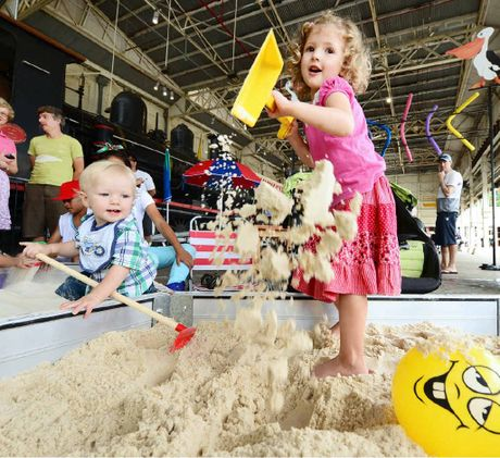 LOVING THE SAND: Sophie and Ben West enjoy the beach theme activities at The Railway Workshops Museum.
