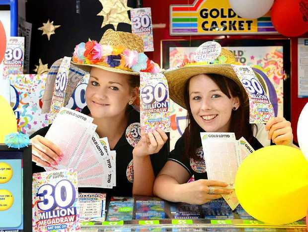 TAKE YOUR CHANCE: Bryanna Cochrane and Katie Brown, of Raceview News, were busy with customers buying entries in Saturday night's $30 million lotto draw.