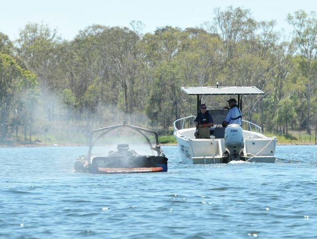 A smoking boat is towed to the shore at Atkinson's Dam on Wednesday.