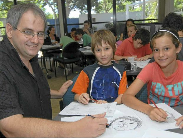 FINE LINE: Cartoonist Harry Bruce shows Luke Troxell and his sister Stephanie some tricks at a cartoon workshop.