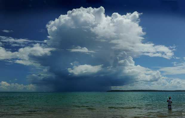 Holidaymaker Matt Warren tried his luck with a rod at Urangan as storm clouds built over Fraser Island last week.