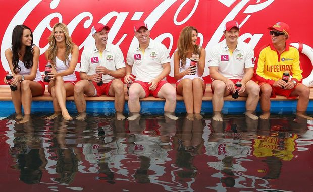 "(C) Shane Watson, David Warner and Michael Hussey of Australia pose with models during a ""COCA-COLA Beach at the Cricket"" event at Sydney Cricket Ground on January 2, 2013 in Sydney, Australia."