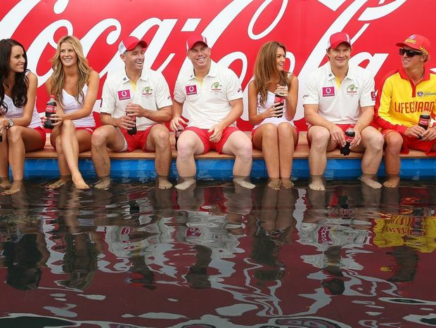 """(C) Shane Watson, David Warner and Michael Hussey of Australia pose with models during a """"COCA-COLA Beach at the Cricket"""" event at Sydney Cricket Ground on January 2, 2013 in Sydney, Australia."""