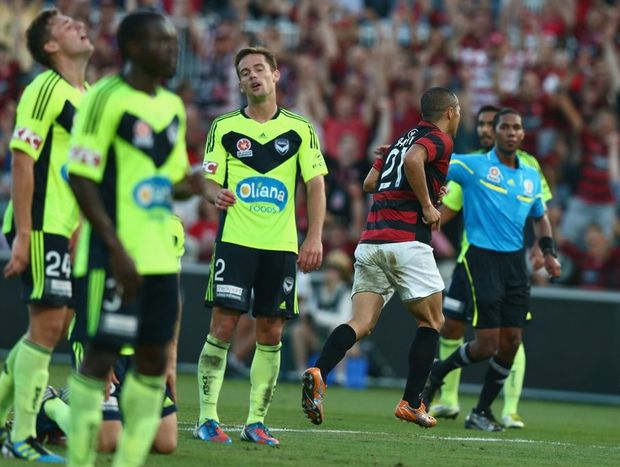 The Victory players react as Shinji Ono of the Wanderers runs to celebrate scoring a goal during the round 14 A-League match between the Western Sydney Wanderers and the Melbourne Victory at Parramatta Stadium on January 1, 2013 in Sydney, Australia.