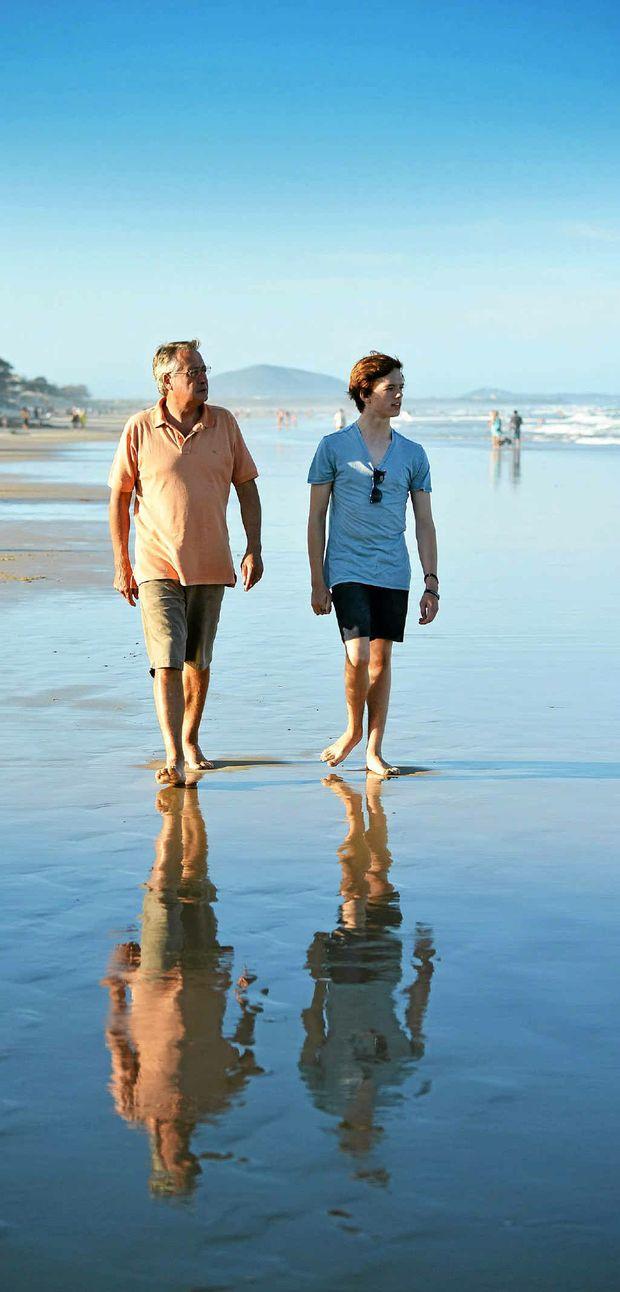 Federal Treasurer Wayne Swan and his son Matt enjoy a walk on the beach while holidaying on the Sunshine Coast.
