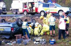 Rescuers work to save the life of a woman who rolled her car on the Bruce Hwy.