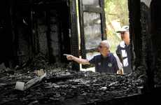 Toowoomba Jazz Club members Bill White and Pat Murphy inspect the burnt ruins of their former clubhouse.