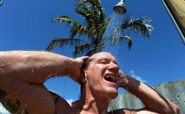 Ray Baxter, of Pottsville, taking a shower at Kingscliff Beach after cooling off in the surf.