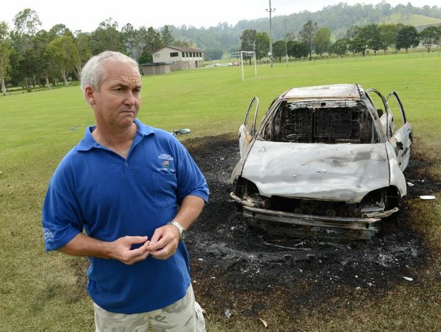 Paul Albertini president of the Lismore Thistles Soccer Club pictured on one of the playing fields and the burnt out car.
