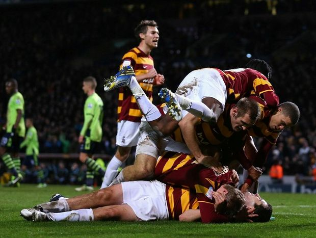 Carl McHugh of Bradford City (grounded) celebrates with team mates after scoring their third goal during the Capital One Cup Semi-Final 1st Leg match between Bradford City and Aston Villa at Coral Windows Stadium on January 8, 2013 in Bradford, England.