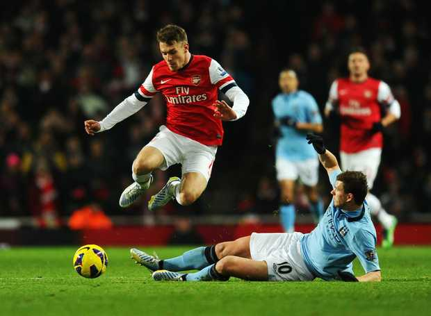 Aaron Ramsey of Arsenal is tackled by Edin Dzeko of Manchester City during the Barclays Premier League match between Arsenal and Manchester City at Emirates Stadium on January 13, 2013 in London, England.