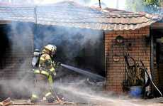 Firefighters attend to the scene of the house fire in Piringa St, Wurtulla.