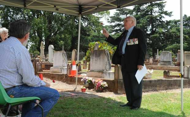 Jim Danskin of the RSL funeral committee describes the significance of the poppy before placing it beside Clyde French's ashes.