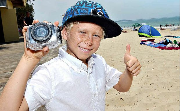 Seven-year-old Jakeb Spicer gives the thumbs up after he claimed his camera, which he lost it in the Noosa surf.