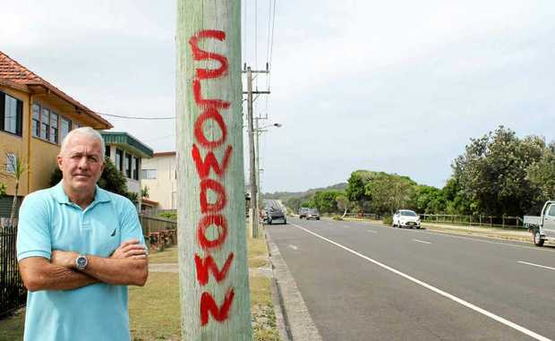 "CLEAR MESSAGE: Local resident James Warren and one of the telegraph poles on Shelly Beach Rd with the words ""Slow down"" painted on them."
