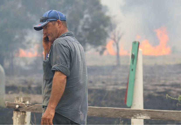 CONTAINED: Fire rages near the Capricorn Hwy in Emerald as a resident co-ordinates a plan of attack with the rural fire service.