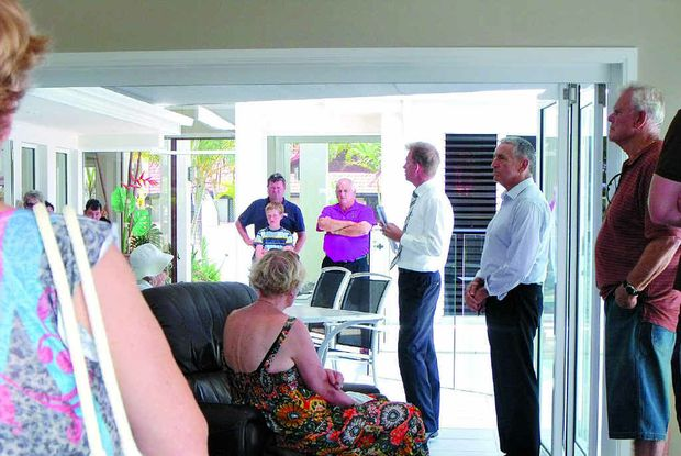 Selling, selling: Ray White Caloundra's Andrew Garland calls the auction of 16 Reliance Pl, Pelican Waters. The waterfront house sold under the hammer for $1.2m with Ken Callec