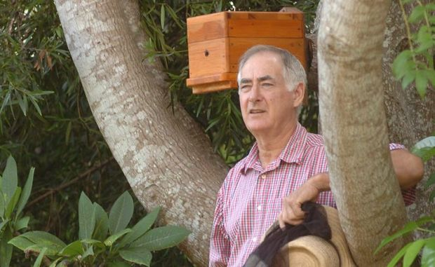 Native beekeeper Doug Irvine with one of his hives made with 130-year-old cypress pine. This hive is an example of inducing bees to colonise in a vacant box by attaching it to a hollow tree.
