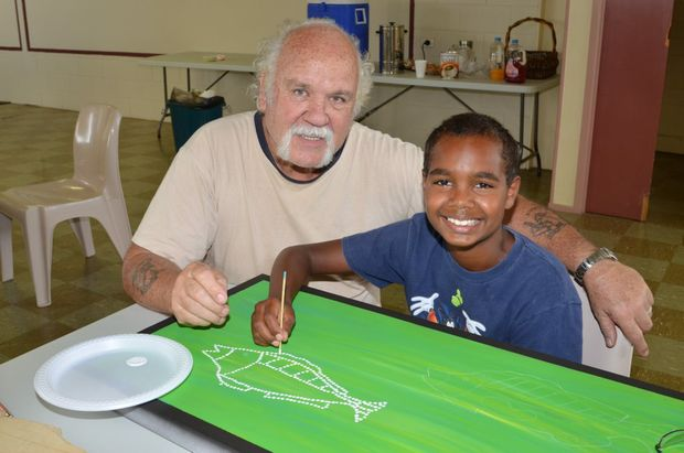 ART ATTACK: Roger Saunders teaches Anquon Sandow, 11, how to paint.