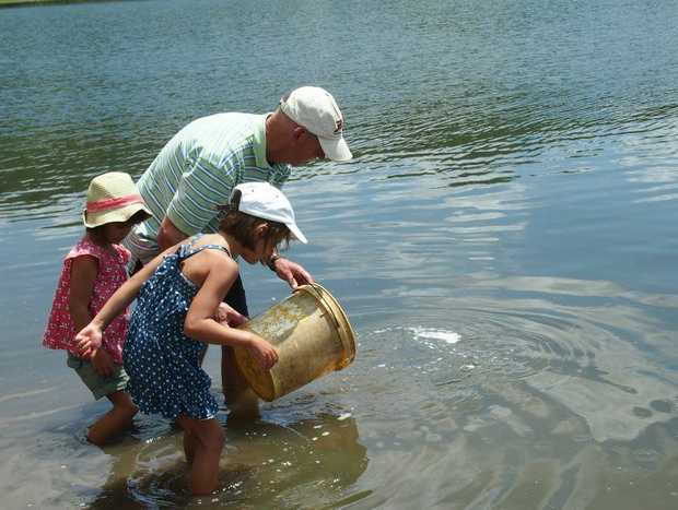 Young helpers Amelia and Rose Ramia helping Peter Taylor this week restock Cressbrook Dam with fingerlings.