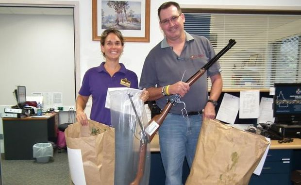 Senior Constable Elissa Dodd and Constable David Mays with guns, stolen property and two large bags of cannabis seized in raids.