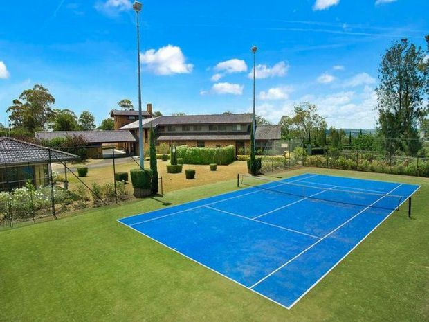 A full-size tennis court is set in the manicured grounds.