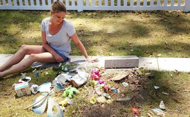 Cassandra Wilson surveys the damage at her baby boy's grave this week.