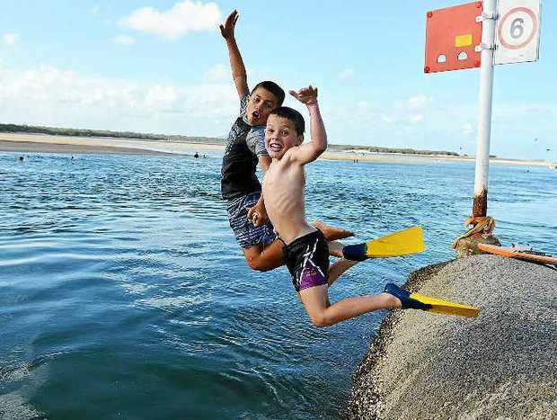 Cousins Teihi Blair and Jacob Blair keep their cool in the Maroochy River at Cotton Tree.
