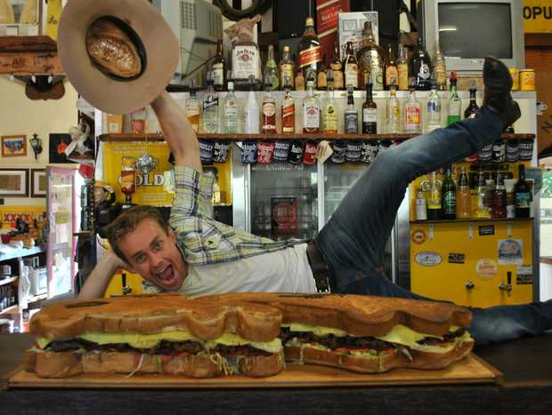 MACK ATTACK: Sunrise weatherman Grant Denyer hams it up for the camera with the Nindigully Pub's 24-kilogram goliath, the Real Big Mack.