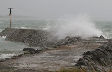 Waves crash over the breakwater at the entrance to Ross Creek, Yeppoon.
