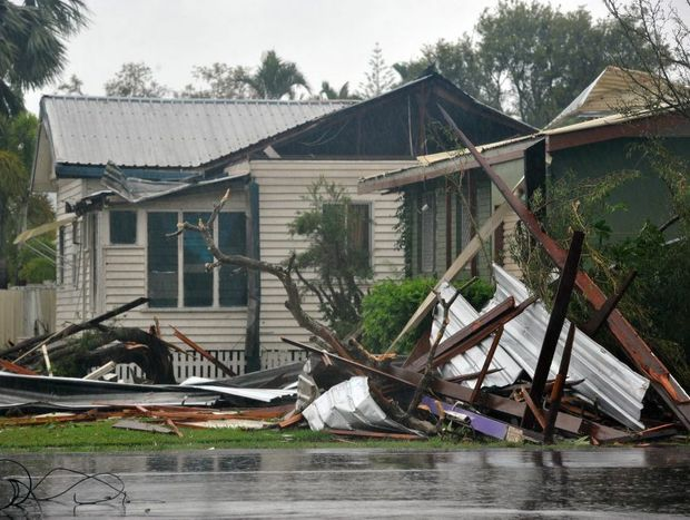 Bargara gets slammed by a tornado, uprooting trees, downing powerlines and ripping roofs off houses. Photo: Max Fleet / NewsMail