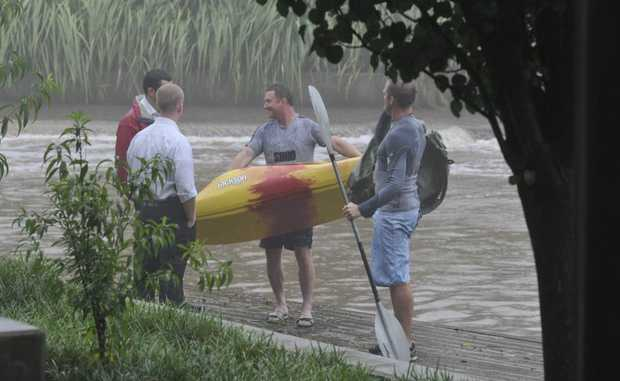 Two plain-clothes detectives tell West Creek paddlers to move along as the rain pours down on Australia Day.