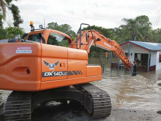A 12 tonne excavator moves units to higher ground as the Mary River rises.